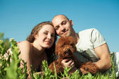 Portrait of happy couple with dog lying on the grass — Stock Photo