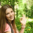 Close up portrait of girl at the park showing okay symbol. — Stock Photo