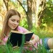 Girl reading book, while lying in the grass at park — Stock Photo