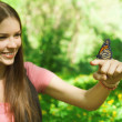 Butterfly sitting on the finger of a young woman in the park — Stock Photo