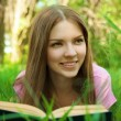 Close up portrait of smiling girl reading book at the park — Stock Photo #25128751
