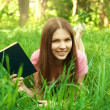 Close up portrait of smiling girl reading book at the park — Stock Photo