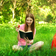 Beautiful young girl-student read the book at the park with an a — Stock Photo