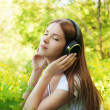 Happy girl with headphones enjoying nature at sunny day. — Stockfoto
