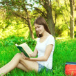 Portrait of beautiful young girl reading a book in the park at s — Stock fotografie
