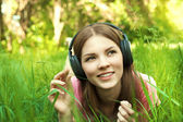 Close up portrait of Pretty young girl listening music lying at — Stock Photo