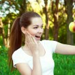 Girl holding apple and looking surprised, outdoor — Stock Photo