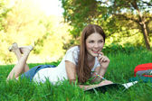 Young woman college student with book and bag studing in a park — Stock Photo