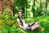 Girl reading a book, sitting under the tree at the park — Stock Photo