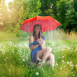 A girl caught in a rain shower under her umbrella — Stock Photo