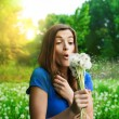 Girl blowing dandelion on green field — Stockfoto