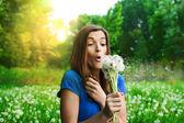 Girl blowing dandelion on green field — Stock Photo