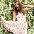 Cute girl in floral dress over bush of white flowers — Stock Photo