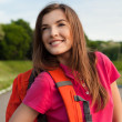 Female student at the park with backpack dreaming about future - Stock fotografie