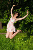 Girl in short floral dress jumping high at the park — Stock Photo