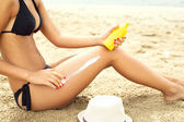 Woman moisturizing applying sun cream on her tanned body and leg — Stock Photo