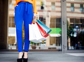 Girl holding shopping bags in one hand, legs in blue trousers — Stock Photo