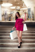 Shopping young woman in shopping mall — Stock Photo