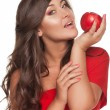 Portrait of girl with red apple in red dress, over white backgro — Stock Photo