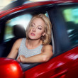 Attractive blonde young woman driving her red car and look out o — Stock Photo #27706889