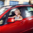 Attractive blonde young woman driving her red car and look out o — Stock Photo