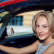 Portrait of young pretty blonde woman in the red car — Stock Photo