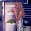 Woman looking in fridge at night — Stock Photo
