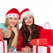 Women in santa hats with gift boxes — Stock Photo #48454233