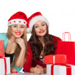 Women in santa hats with gift boxes — Stock Photo