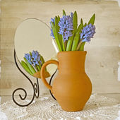 Bunch of hyacinths in a clay pot on old paper — Stock Photo