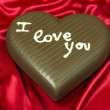 Chocolate heart on red satin — Stock Photo #22808374