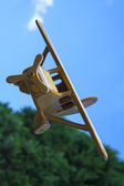Wooden toy plane in mid-air — Stock Photo