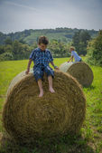 Boys on round hay bales — Stock Photo