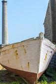 Old boat near lighthouse — Stock Photo