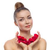 Retrato de una bella mujer con pétalos de rosas en las manos — Foto de Stock