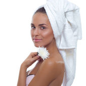 Portrait of a beautiful young woman with a flower in his hand and a towel on her head — Stock Photo