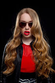 Glamorous portrait of a young woman in glasses with long curly hair — Stock Photo