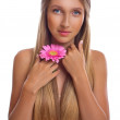 Portrait of a beautiful young woman with long hair and flower in hand — Stock Photo #26374971