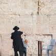 Rabbi and his little son at the Wailing wall - Stock Photo