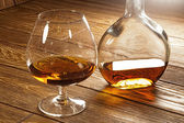 A glass of brandy and a bottle on a brown table — Stock Photo