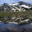Stock Photo: Mountain reflecting in pond