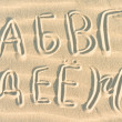 Russian letters written on sand — Stock Photo