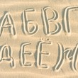 Russian letters written on sand — Stock Photo #33996435