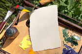 Textured paper on palette lying on painter case on the grass — Stock Photo