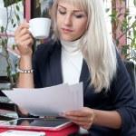 jovem mulher assistindo documentos comerciais e bebendo café — Foto Stock