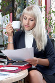 Young woman watching business papers and drinking coffee — Stock Photo