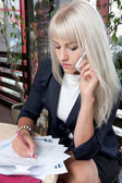 Woman talking to cell phone and working with business papers — Stock Photo