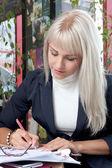 молодая женщина, писать на ее деловые бумаги — Стоковое фото