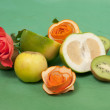 Roses and fruits on a green background — Stock Photo