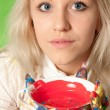 Portrait of an attractive girl with colorful hands a cup of red paint — Stock Photo